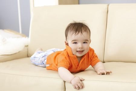 impish: Cute baby boy lying on sofa, smiling, looking at camera.