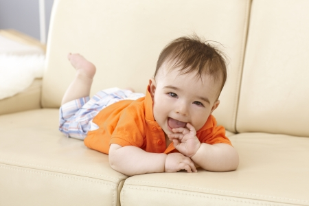 impish: Beautiful baby boy lying on sofa, smiling happy with hand in mouth.