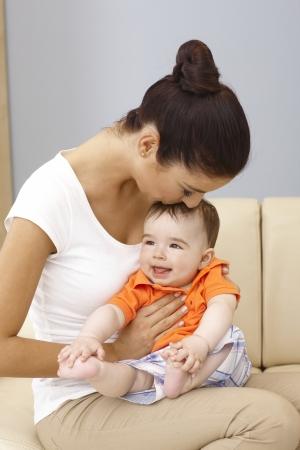 be kissed: Giovane madre felice che tiene bambino in braccio, baciare la testa. Archivio Fotografico