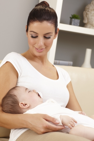 Young mother holding sleeping baby in arms, looking affectionate. photo