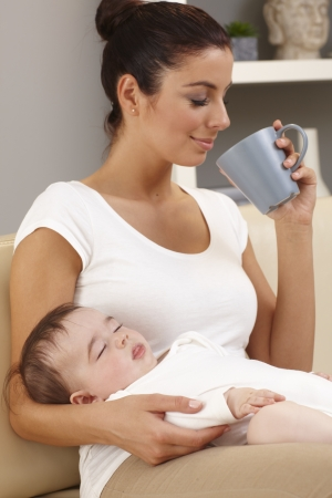 mums: Young mother drinking tea in peace while baby sleeping in her arms. Stock Photo