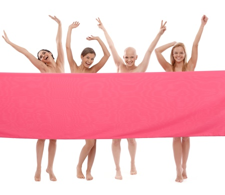 cancer prevention: Young happy women behind pink textile laughing.   This is a free image, part of a charity project. Models and the staff worked for free to support breast cancer awereness campaigns worldwide.