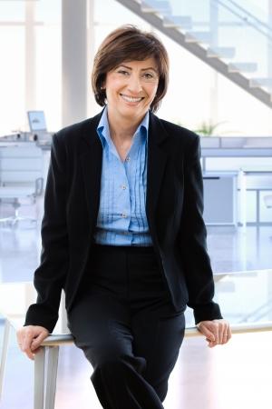 mujeres sentadas: Feliz de negocios maduros en la oficina sentado en el escritorio, sonriendo.