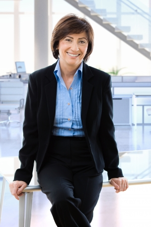 Happy mature businesswoman in office sitting on desk, smiling.