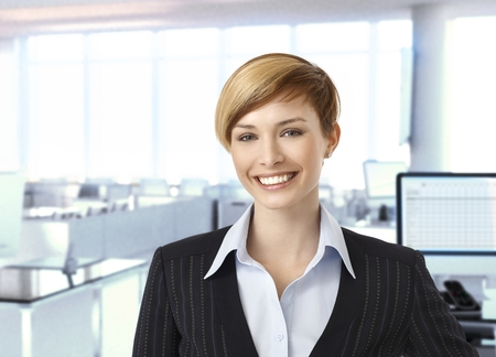 gingerish: Happy businesswoman in corporate office Stock Photo