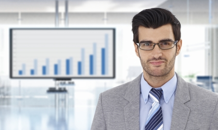 financials: Portrait of confident young businessman at office with financial graph on TV.