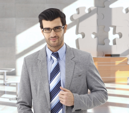Confident businessman at office reception, puzzle decoration in background. photo
