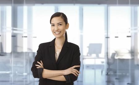 mujer sola: Retrato de la sonrisa joven empresaria asi�tica en la oficina. Espacio para el texto.