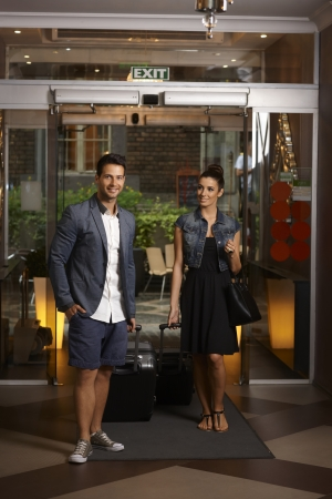 arriving: Young couple arriving at hotel with suitcases, smiling. Stock Photo