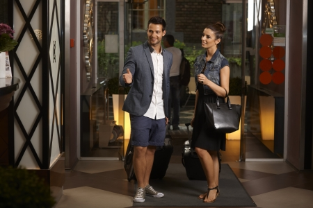 arriving: Young couple arriving at hotel lobby, having suitcases, smiling, looking for reception desk.