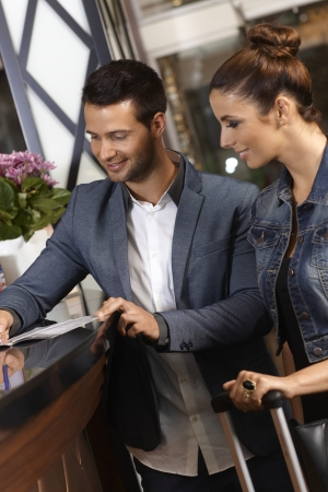 checking in: Young couple checking in at hotel reception upon arrival. Stock Photo