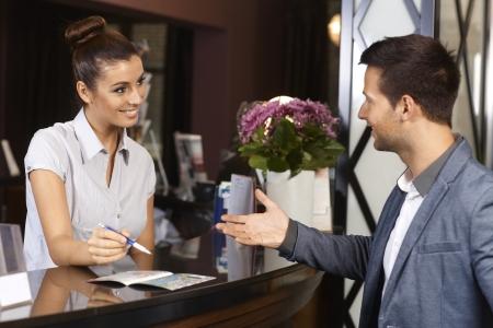 recepcionista: Recepcionista feliz e invitado a hablar en la recepción del hotel. Foto de archivo