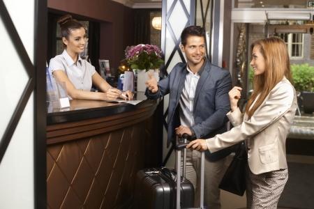 hospedaje: Pareja joven a su llegada en la recepción del hotel.