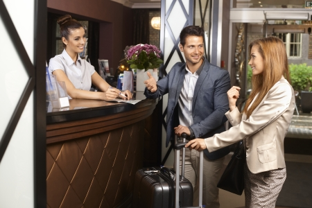 Young couple upon arrival at hotel reception. Stock Photo - 22308149