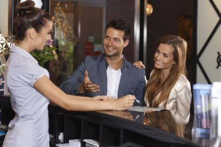 幸せなカップルは、ホテルのフロントで観光情報を受け取る、すべてハッピー笑顔。 写真素材