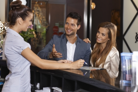 wedding guest: Happy couple receiving tourist information at hotel reception, all smiling happy. Stock Photo