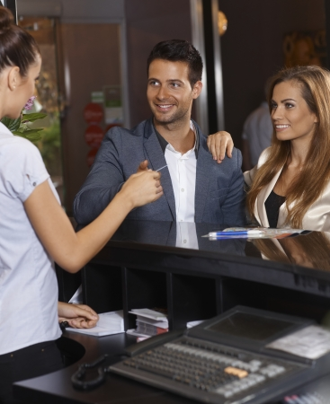 standing reception: Guests receiving key card from receptionist at hotel. Stock Photo