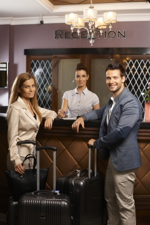 Happy young couple standing at hotel reception surrounded by suitcases upon arrival photo
