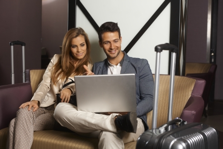 Young couple sitting on sofa at hotel lobby upon arrival, using laptop computer