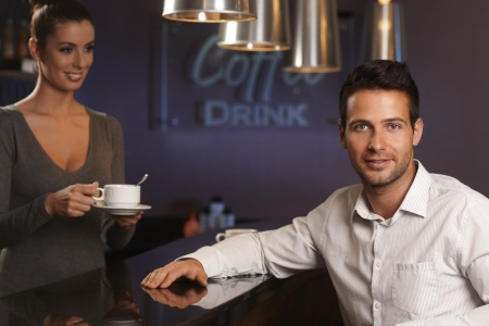 Portrait of handsome young businessman sitting in bar photo