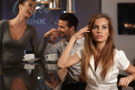 Unhappy young woman sitting in bar, boyfriend flirting with waitress at background. Imagens
