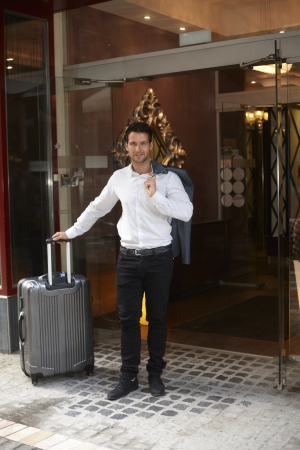Young businessman leaving hotel, having big suitcase, smiling.