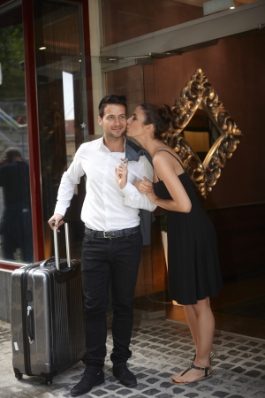 be kissed: Loving couple leaving hotel, woman kissing man, having suitcase.