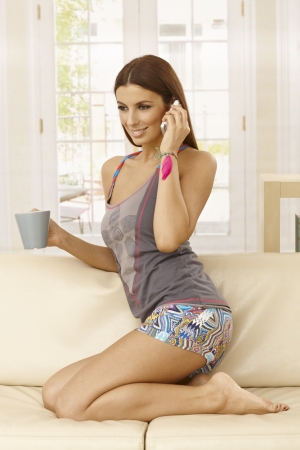 Pretty girl talking on mobilephone at home, kneeling on sofa, smiling, looking away. photo