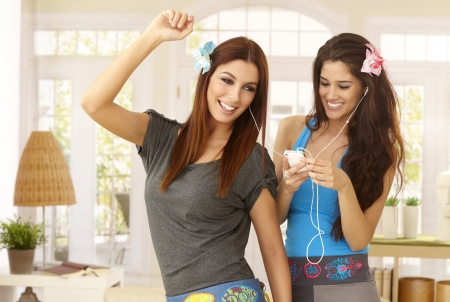 room mate: Happy girls listening to music on mp3 player, dancing at home in living room, smiling. Stock Photo