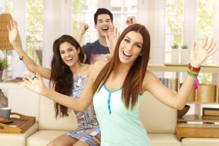 arms wide: Happy giovani divertirsi a casa, ridendo braccia spalancate, guardando alla fotocamera.