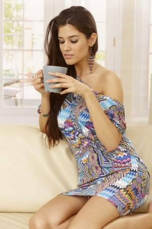 Pretty young woman kneeling on sofa at home, drinking tea. photo