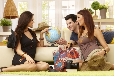 Young companionship planning summer holiday, poiting destinations on globe. photo
