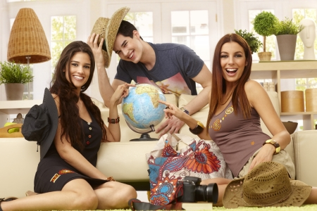 Happy young roommates planning summer holiday, having globe, smiling. photo