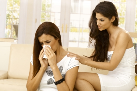 two stroke: Young woman consoling crying friend at home. Stock Photo