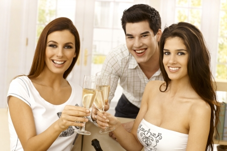 Closeup portrait of happy young people clinking with champagne flute, smiling, looking at camera. photo