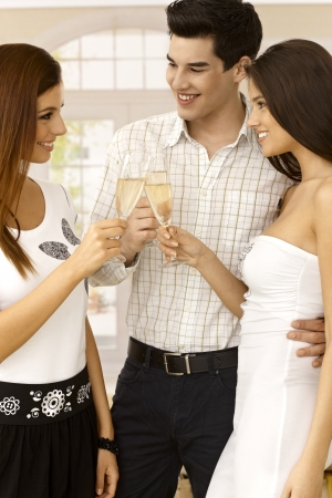 Young friends clinking with champagne flute, celebrating at home, smiling happy. photo