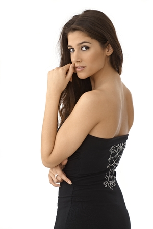 looking over shoulder: Portrait of attractive young woman in black dress, looking over the shoulder. Stock Photo