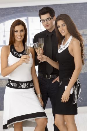 compa�erismo: Elegante joven compa��a bebiendo champ�n, vasos tintineantes.