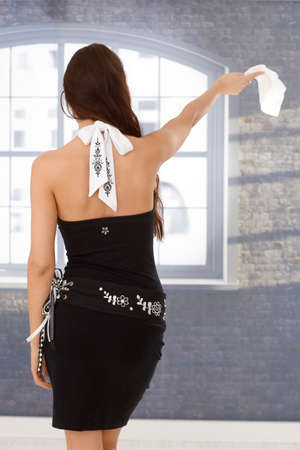 hanky: Back view of pretty woman in fancy mini dress, waving with hanky. Stock Photo
