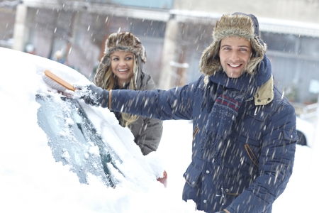 Happy young couple standing in snowfall, brushing off snow from car.