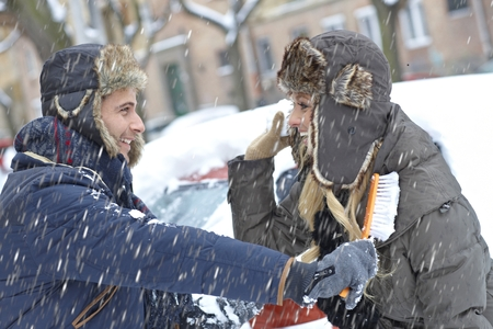 Young loving couple having fun in snowfall, brushing off car, throwing snowball. photo