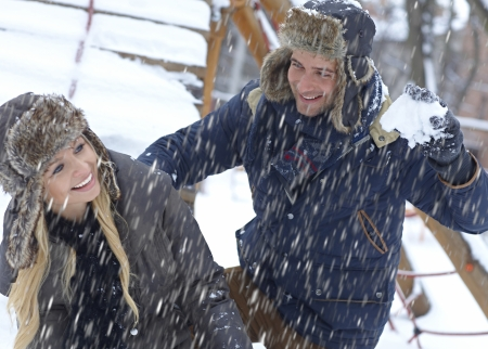 Outdoor photo of loving couple having fun at wintertime in snowfall. photo