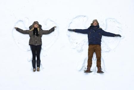 Pareja joven tumbado en la nieve fresca, haciendo ángeles de nieve que se divierten. Foto de archivo - 22601533