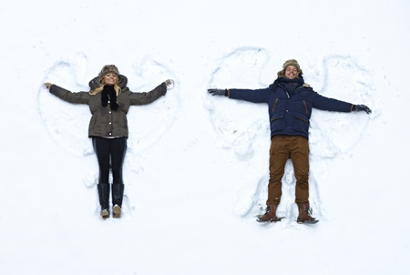 woman laying: Young couple lying in fresh snow, making snow angels having fun.