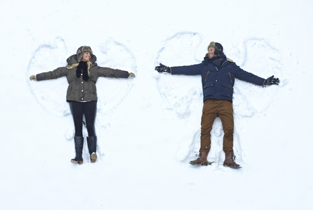 Loving couple lying in fresh snow, smiling happy, making snow angels. Imagens