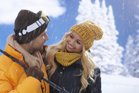Young loving couple smiling happy, hugging at wintertime, skiing. photo