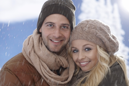 couple winter: Close-up winter portrait of young loving couple hugging in snowfall. Stock Photo