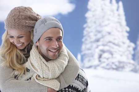 snow woman: Portrait of happy loving couple embracing at wintertime outdoors.