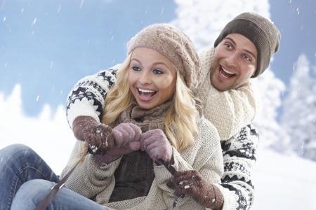 sledging: Giovane coppia divertirsi inverno, slittino, ridendo.