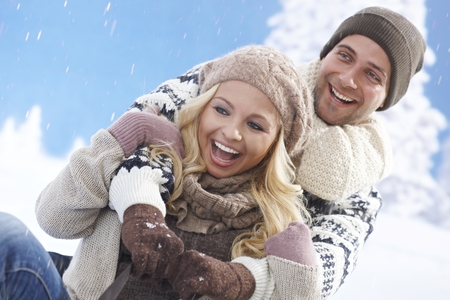 Happy loving couple sledging at wintertime outdoors, laughing. photo